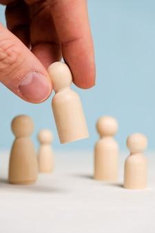 Une main tient une figurine en bois sur un fond bleu. concept de construction d'équipe. fermer.