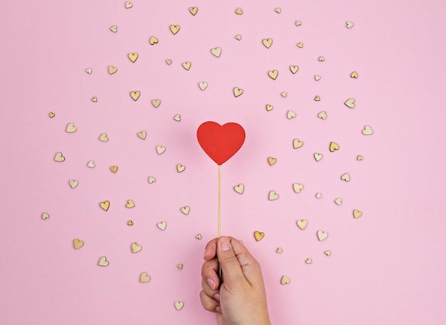 Main tient grand coeur en bois rouge sur fond rose