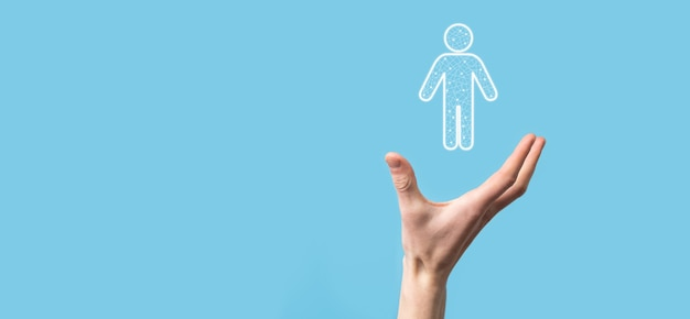 Main tient l'icône de personne homme sur une surface de ton sombre