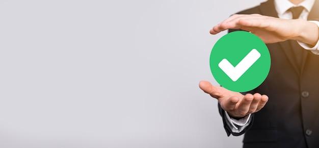 La main tient l'icône verte coche, signe de coche, icône de coche, signe de droite, bouton de coche verte de cercle, fait. sur fond gris. bannière. espace de copie. place pour le texte.