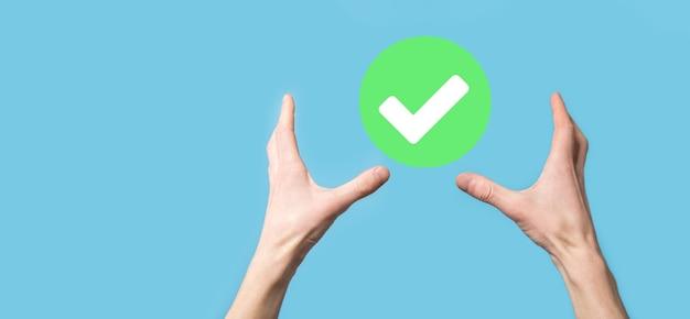 La main tient l'icône verte coche, signe de coche, icône de coche, signe de droite, bouton de coche verte de cercle, fait. sur fond sombre. bannière. espace de copie. place pour le texte.