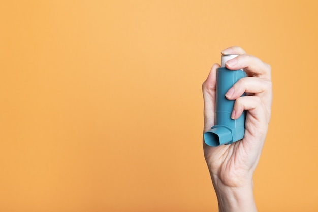 La main tient l'inhalateur bleu pour traiter l'asthme d'isolement sur le fond orange