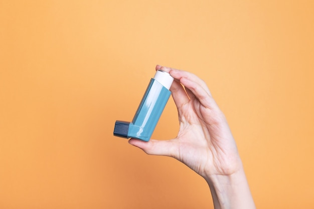 La main tient l'inhalateur pour traiter l'asthme. journée mondiale de l'asthme. concept de soins allergiques
