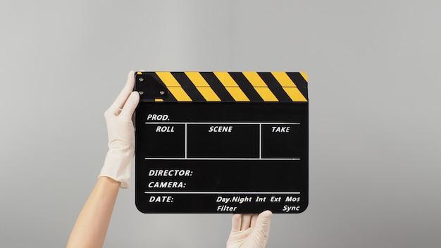 La main tient le jaune avec la couleur du panneau de clapet noir et porte un gant médical blanc. il est utilisé dans la production vidéo et l'industrie cinématographique sur fond gris.