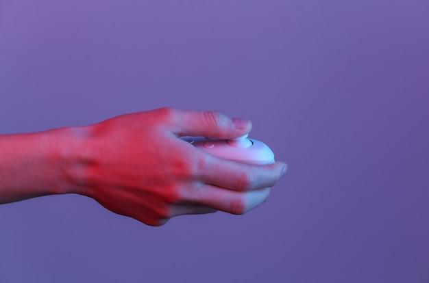 La main tient le joystick moderne en néon bleu.