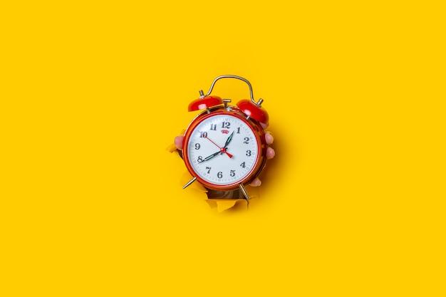 La main tient une montre rouge dans un trou sur un fond jaune déchiré.