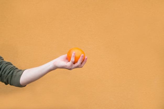 La main tient une orange sur le mur d'un mur orange. fruit du concept