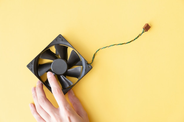 Main tient un ordinateur portable op pc fan sur le fond jaune avec copie espace