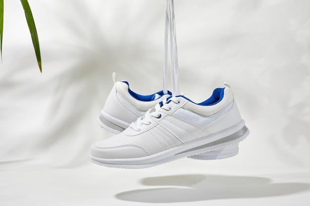 La main tient par des lacets de baskets blanches. main tenir des chaussures de sport sur fond blanc avec des feuilles de palmier. concept de vacances d'été.
