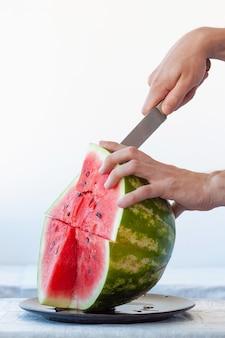 Une main tient une pastèque rouge mûre, l'autre tient un couteau et coupe un morceau de pastèque. cadre vertical