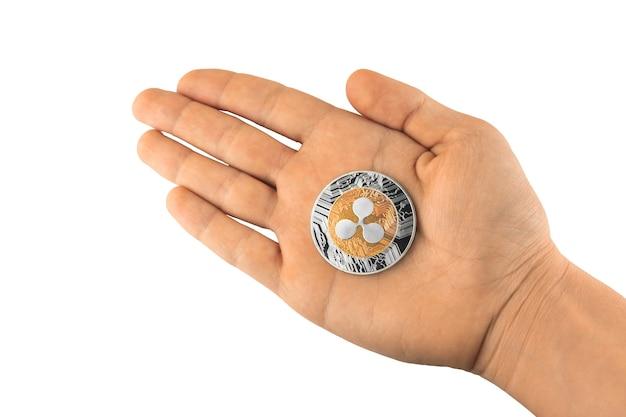 La main tient la pièce d'ondulation isolée sur fond blanc, photo de crypto-monnaie