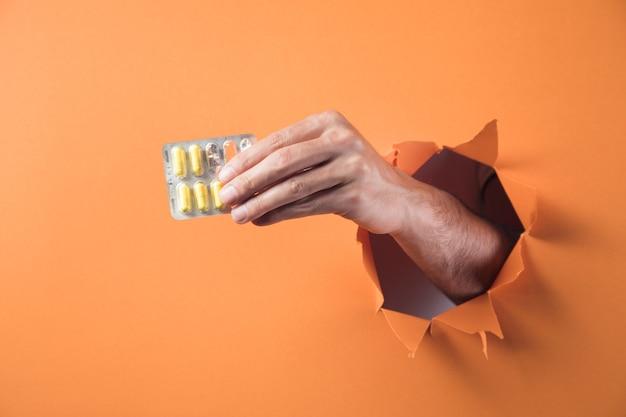 Main tient des pilules sur fond orange