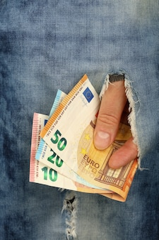Main tient plusieurs billets de monnaie papier euro de valeur différente dans le trou de déchirure de jeans, low angle view