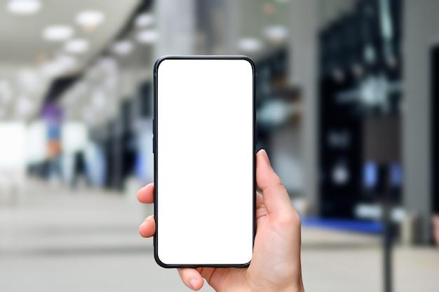 La main tient un smartphone avec un espace de copie et l'arrière-plan de l'immeuble de bureaux.
