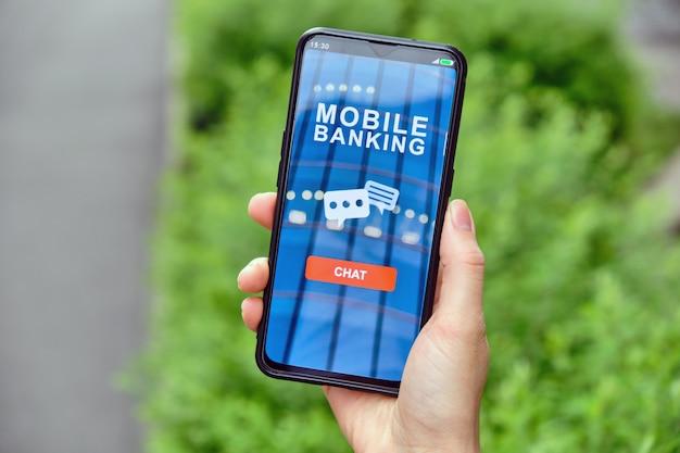 Main tient le smartphone avec une interface bancaire mobile et un bouton de chat pour communiquer avec les icônes
