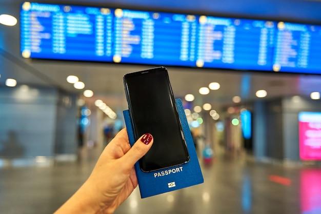 Une main tient un smartphone et un passeport pour voyager à l'étranger dans le contexte d'un panneau d'information à l'aéroport.