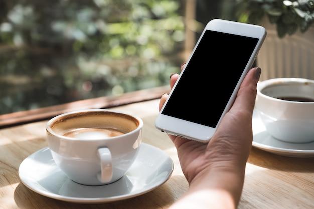 Une main tient un smartphone et des tasses à café sur la table