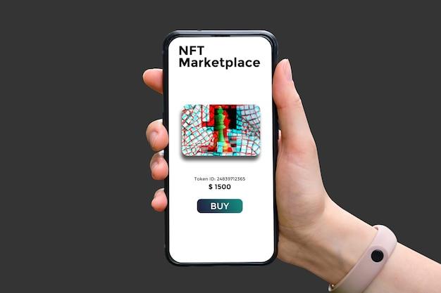 Main tient le smartphone avec le type de marché cryptographique nft avec vente d'art.
