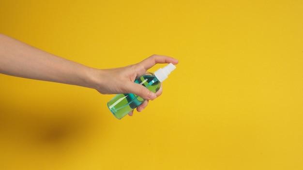 La main tient un spray d'alcool sur fond blanc.