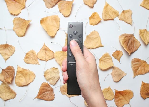 La main tient la télécommande du téléviseur avec des feuilles tombées. vue de dessus