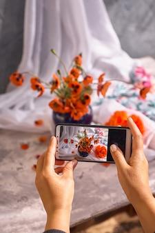 La main tient le téléphone et photographie la nature morte des coquelicots