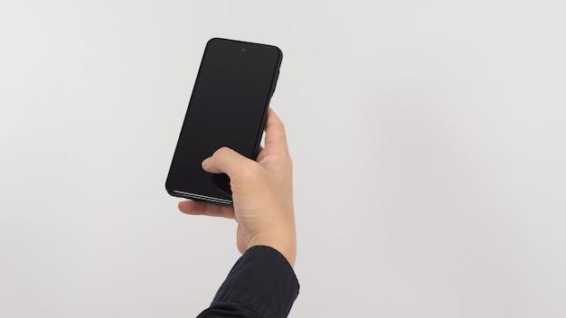 La main tient le téléphone portable isolé sur fond blanc.