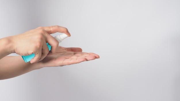 La main tient le vaporisateur d'alcool et se lave l'autre main sur fond blanc.