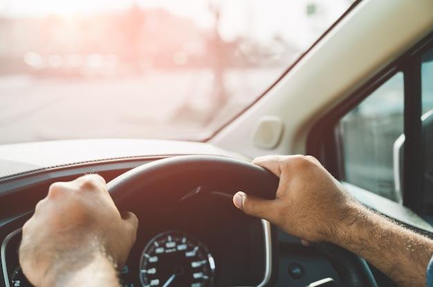 La main tient le volant de la voiture conduite sûre