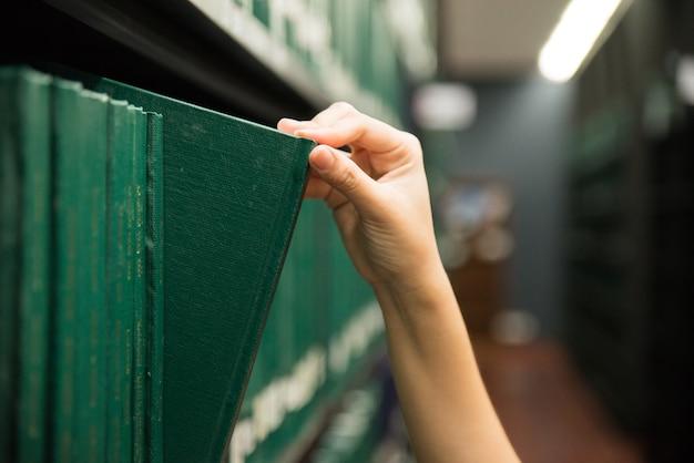 Main tirant un livre de thèse sur l'étagère dans la bibliothèque. livres de couleurs vertes.