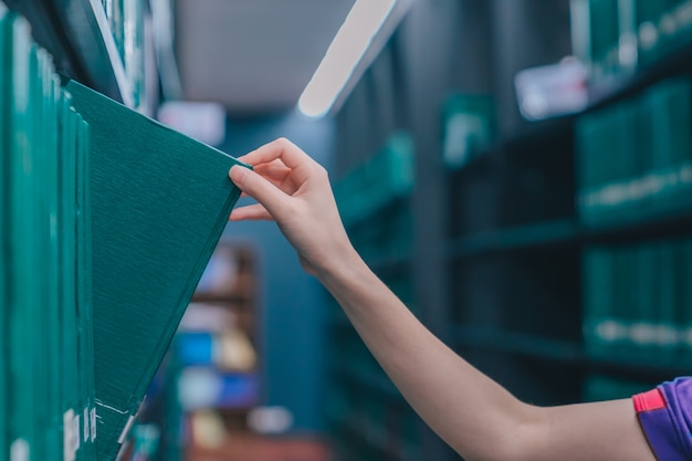 Main tirant un livre de thèse sur l'étagère dans la bibliothèque