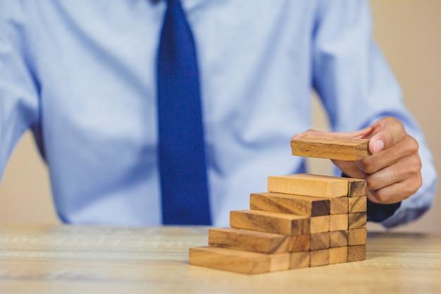 La main en tirant ou en plaçant des blocs de bois sur la tour.