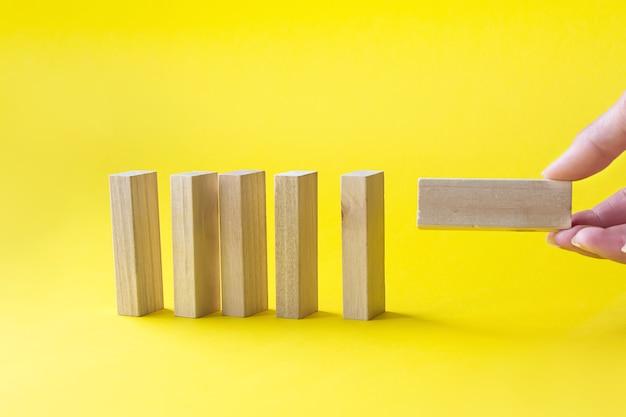 La main tire un bloc de bois du même fond jaune de blocs. leader, individualité, meilleur travailleur
