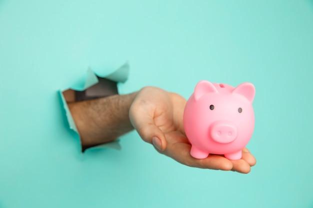 La main avec une tirelire rose à travers un trou de papier. concept financier et commercial.