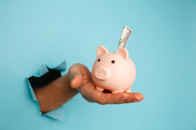 La main avec une tirelire à travers un trou de papier bleu. concept financier et commercial