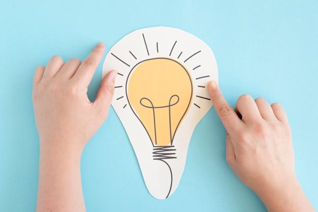 Main touchant une ampoule de papier découpée sur fond bleu
