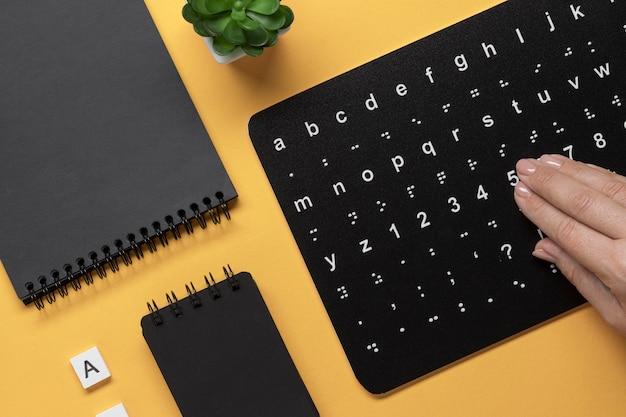 Main touchant le clavier de l'alphabet braille