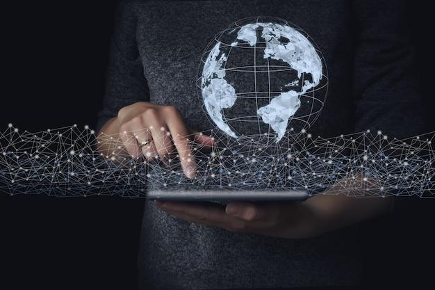Main touchant la connexion au réseau mondial et les échanges de données sur le fond de la planète terre,