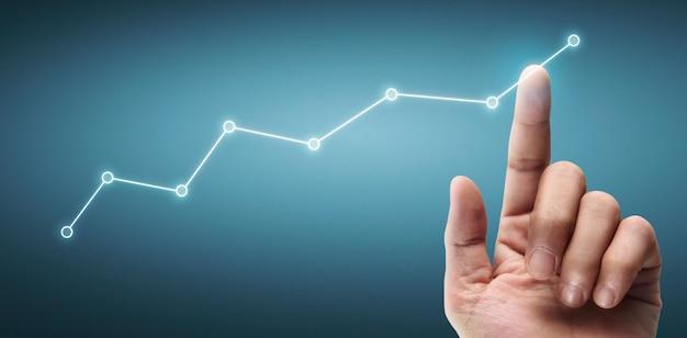 Main touchant un graphique de l'indicateur financier et du tableau d'analyse de l'économie de marché comptable