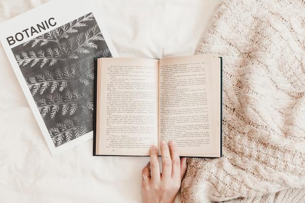 Main touchant le livre sur l'affiche et la couverture sur le drap de lit