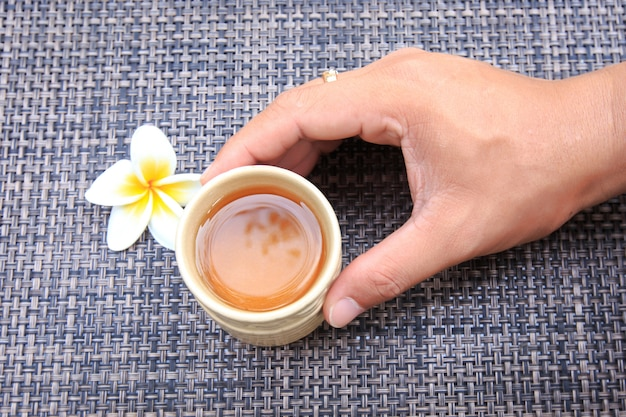 Main touchant la tasse de thé chaud avec fleur de frangipanier sur la natte de bambou