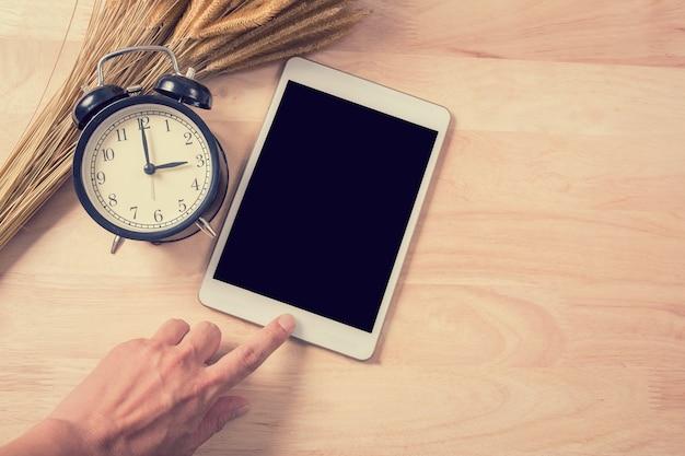 Main touchez la tablette numérique avec écran arrière et horloge rétro sur fond de bois