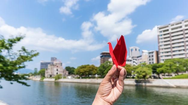 Une main de touriste tenant une grue en papier rouge pliée de grus antigone hiroshima japon