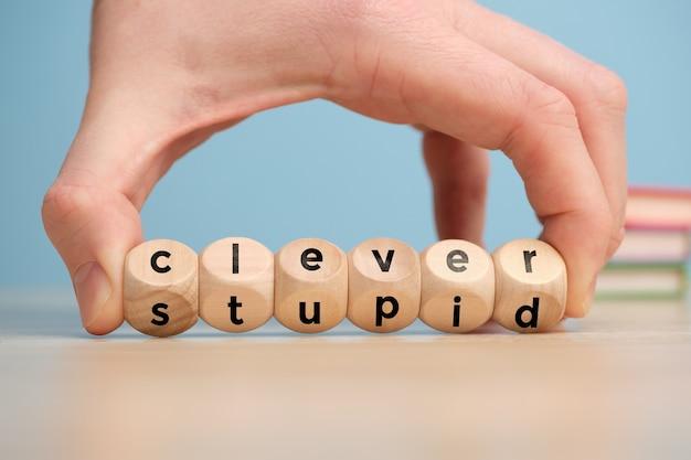 La main tourne les blocs de bois avec l'inscription stupide et intelligente.