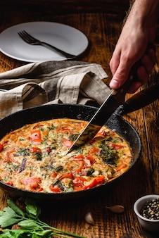Main avec des tranches de couteau frittata de légumes avec brocoli, poivron rouge et oignon rouge dans une poêle en fonte