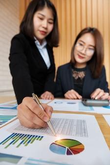 Main de travail d'équipe attrayante tenant un stylo et pointant à la paperasse financière dans l'espace de co-travail.
