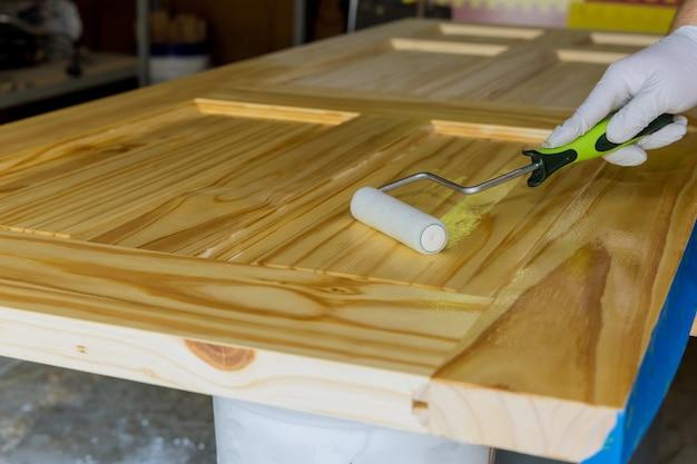 Main de travailleur dans la porte en bois verni de gant pour le laquage utilisant le rouleau de main de la peinture de réparateur
