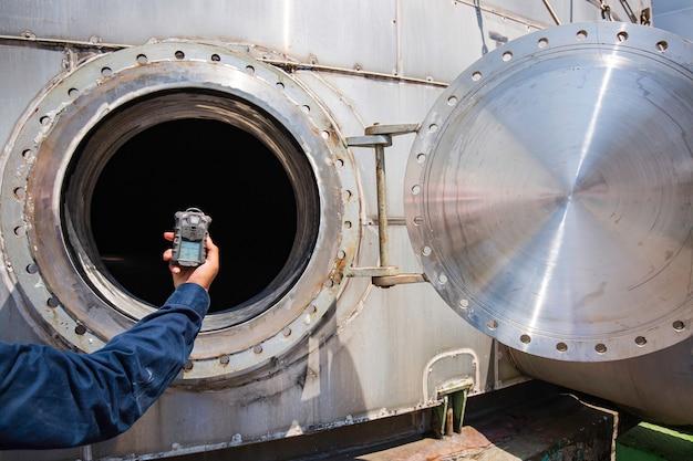 Main de travailleur tenant le détecteur de gaz inspection test de gaz de sécurité au réservoir en acier inoxydable de trou d'homme avant pour travailler à l'intérieur confiné