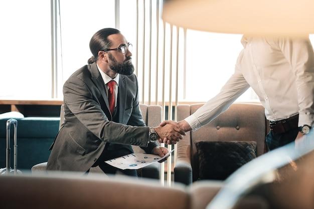 Main tremblante. investisseur riche barbu portant des lunettes serrant la main de son partenaire commercial
