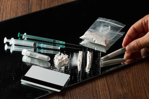 Main avec un tube de dollars et de drogues différentes