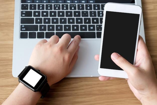 Main en utilisant le smartphone et smartwatch avec fond d'écran blanc pour maquette